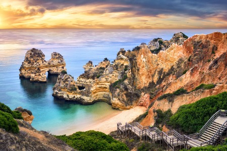 The beautiful Camilo Beach in Lagos, Portugal, with its magnificent cliffs and the blue ocean colorfully lit at sunrise