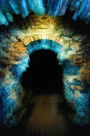 Oude stenen boog verlicht met blauw en geel licht om een magische en mysterieuze toegangspoort tot het donker te creëren