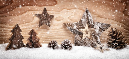 snow and trees: Festive Christmas arrangement with beautiful wooden ornaments on snow in front of a bright wood board background, studio shot