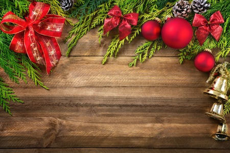 bordering: Christmas arrangement with conifer branches, red bows and baubles, pine cones and gold bells bordering a rustic wood planks background Stock Photo