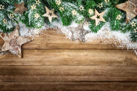 christmas time: Christmas background in natural wood style, rustic, simple and elegant, with a border of fir branches, wooden stars and snow