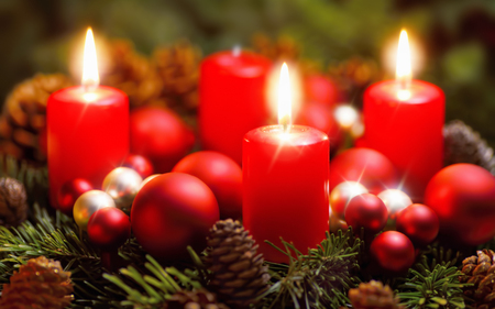 Studio shot of a nice advent wreath with baubles and three burning red candles Stock Photo