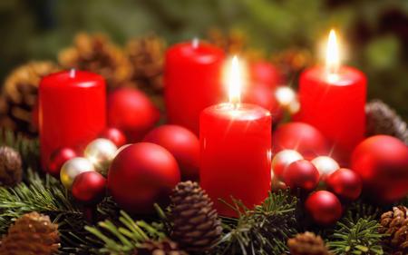 Studio shot krásného adventního věnce s cetkami a dvěma hořícími červenými svíčkami Reklamní fotografie