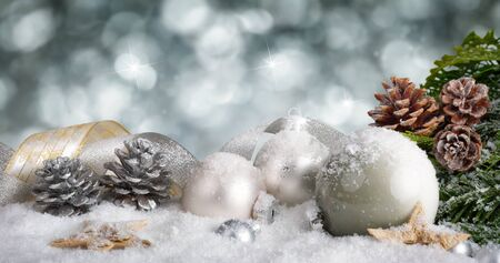 christmas balls: Elegant Christmas arrangement with snow covered silver baubles, nicely curved ribbons and pine cones, with glittering bokeh background
