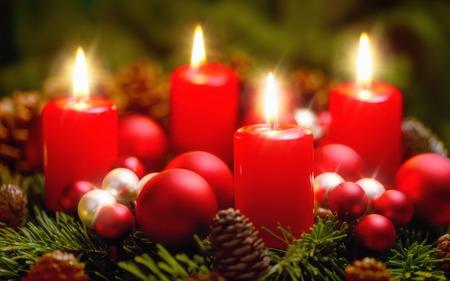 Studio-Aufnahme von einem schönen Adventskranz mit Kugeln und vier brennende rote Kerzen