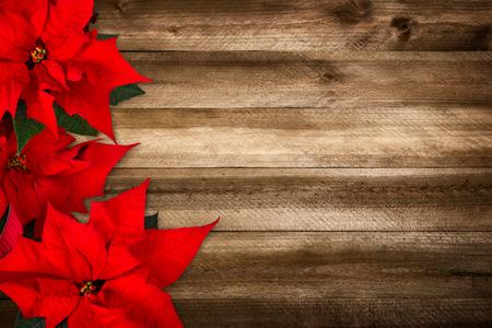 Kerst achtergrond bestaat uit houten planken en poinsettia, met warme kleuren en mooie vignettering