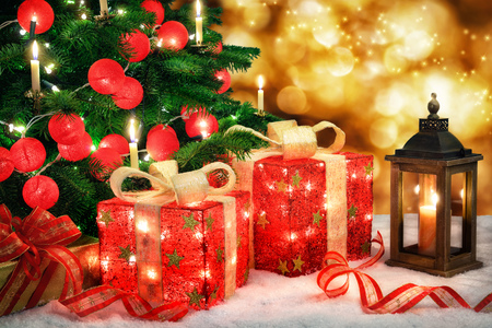 Shiny Christmas scene with a Christmas tree and illuminated red baubles, ornamental gift boxes with lamps, a lantern and bokeh lights background Stockfoto