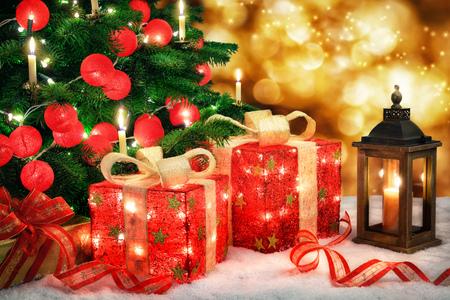 Glanzende Kerstmis scène met een Kerstboom en verlichte rode snuisterijen, sieraden geschenkdozen met lampen, een lantaarn en bokeh lichten achtergrond Stockfoto