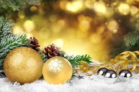 ornamental background: Glamorous Christmas scene with gold ornaments, fir branches and pine cones on snow and defocused shiny golden lights in the background Stock Photo