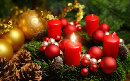 candela: Colpo di studio di una bella corona di Avvento con palline e una candela rossa ardente