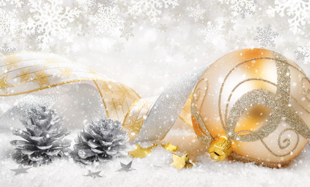 silver: Elegant Christmas arrangement with a beautiful gold bauble, nice ribbons, silver cones, lots of snow and ornamental large snowflakes in the background Stock Photo