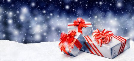 free background: Silver Christmas or birthday gift boxes with red bows in snow, with snowy night background, panorama format Stock Photo