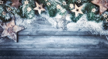 simple border: Blue gray Christmas background in natural wood style, rustic, simple and stylish, with a border of fir branches, wooden stars and snow