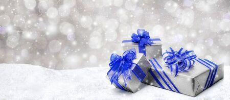 snowflake background: Silver Christmas or birthday gift boxes with red bows in snow, with snowy night background, panorama format Stock Photo