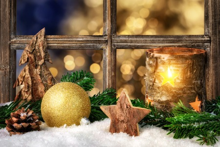 advent time: Christmas, Advent or winter seasonal arrangement on a window sill, decorated with snow, with cozy candle light, ornaments and fir branches Stock Photo