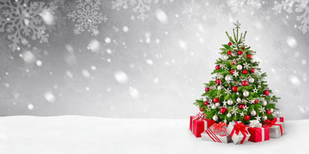 Gorgeous elegant Christmas tree with gifts in red and silver on a panoramic snow background