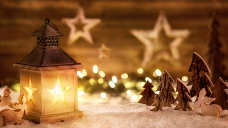 Cozy Christmas arrangement with beautiful wooden ornaments on snow in the warm candlelight of a nice lantern, low-key studio shot Standard-Bild