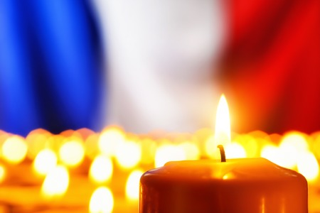 french: Lots of candles in front of the national colors of France in remembrance of the many victims of terror or to simply symbolize the great French spirit Stock Photo