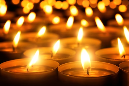 religious: Many candle flames glowing in the dark, create a spiritual atmosphere Stock Photo