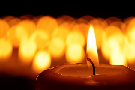 Bougie devant de nombreux candleflames defocused créant une atmosphère spirituelle et en souvenir des êtres chers Banque d'images