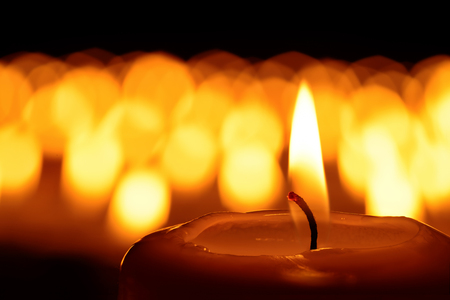 church: Candle in front of many defocused candleflames creating a spiritual atmosphere and in remembrance of loved ones Stock Photo