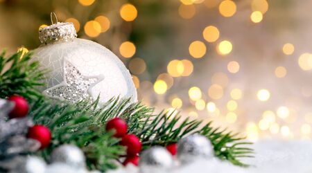 christmas decor: Closeup of Christmas baubles and fir branches on snow, with defocused golden lights in the background