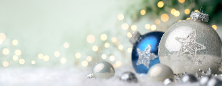 Panoramic Christmas background with nice shiny baubles on snow and defocused lights in the background, with light green copy space