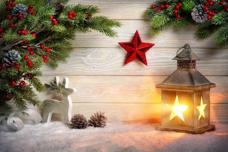 ランタン、モミの枝、赤い星、トナカイ、ろうそくの光で明るい木の板の前に雪のクリスマス シーンのバック グラウンド
