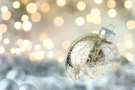 winter celebration: Shiny Christmas bauble closeup with bokeh lights in the background