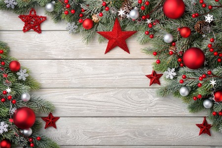 decorated: Christmas background with bright wooden board and fir branches decorated with red and silver baubles and stars - modern, simple and elegant