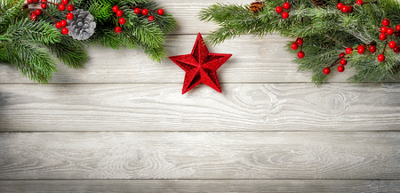gray pattern: Christmas background with fir branches on a bright wooden board and a red star hanging in the middle Stock Photo