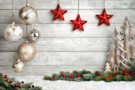De achtergrond van Kerstmis in heldere hout stijl, modern, eenvoudig en elegant, met een grens van kerstballen, dennentakken, sterren, sierbomen en sneeuw
