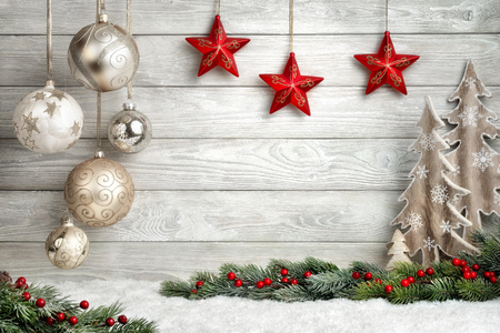 Christmas background in bright wood style, modern, simple and elegant, with a border of baubles, fir branches, stars, ornamental trees and snow Archivio Fotografico