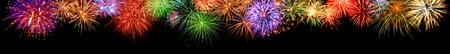 fuegos artificiales: Magníficos fuegos artificiales multicolores como una frontera panorámica extra ancho en el fondo negro, ideal para Año Nuevo u otros acontecimientos de la celebración Foto de archivo