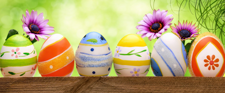 flores moradas: Huevos de Pascua coloridos en una fila, decorado con flores de primavera y la hierba alta, con el fondo del bokeh, formato panor�mico de color verde brillante Foto de archivo