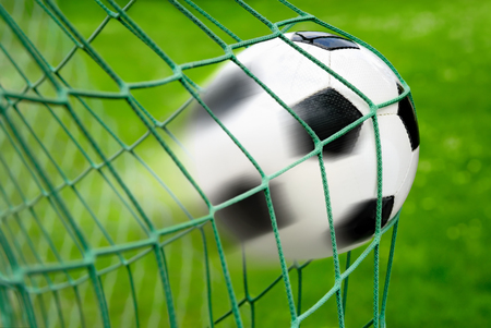 dynamic motion: Football or soccer goal, with the ball leaving a trail in the air as a dynamic motion blur effect Stock Photo