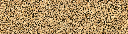 feedstock: Large pile of wood logs make for a nice natural pattern or texture background in panorama format