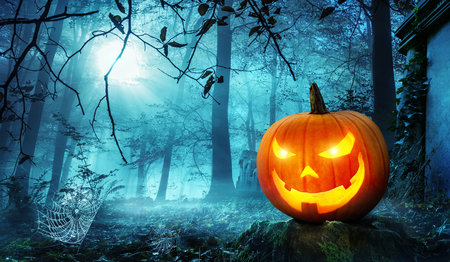 glowing: Glowing Jack o lantern in a creepy old overgrown cemetery with cool blue moonlight