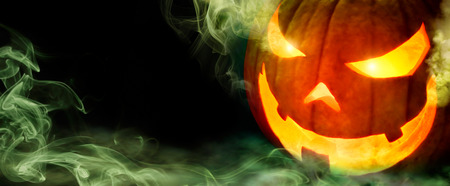 Jack o lantern with evil glowing eyes emanating green smoke, on black panoramic background with copyspace