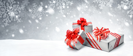 Silver Christmas or birthday gift boxes with red bows in snow, with symbolic snow background, panorama format