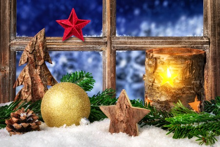 Christmas, Advent or winter seasonal arrangement on a window sill in cozy candle light, decorated with snow, ornaments and fir branches