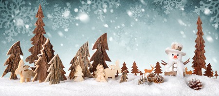 Wooden decoration arranged as a cute winter scene with a snowman, conifer trees, Christmas star, animals and snow, on a snowflakes background