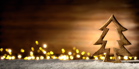 lowkey: Cozy Christmas arrangement with beautiful wooden ornaments on snow in the warm candlelight of a nice lantern, low-key studio shot Stock Photo