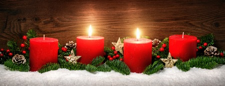 lowkey: Low-key studio shot of elegant advent decoration with fir branches on snow and tow burning red candles, dark wood background