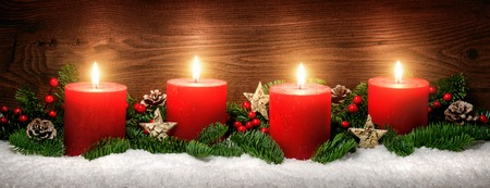 Low-key studio shot of elegant advent decoration with fir branches on snow and four burning red candles, dark wood background