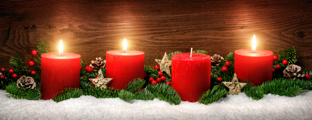 lowkey: Low-key studio shot of elegant advent decoration with fir branches on snow and three burning red candles, dark wood background Stock Photo