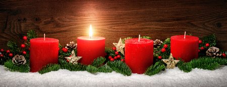 Low-key studio shot of elegant advent decoration with fir branches on snow and one burning red candle, dark wood background Reklamní fotografie - 65438160
