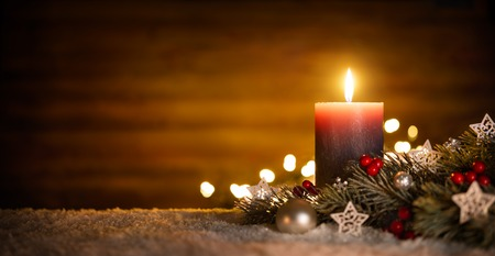 Burning candle and Christmas decoration over snow and wooden background, elegant low-key shot with festive mood