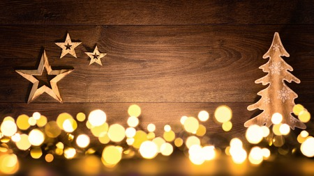 illuminated: Christmas background with wooden ornaments arranged on a dark wood board and bokeh lights shining in the foreground