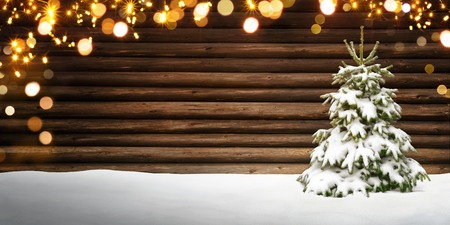 Christmas frame with wooden background, snow covered fir tree and glowing defocused lights